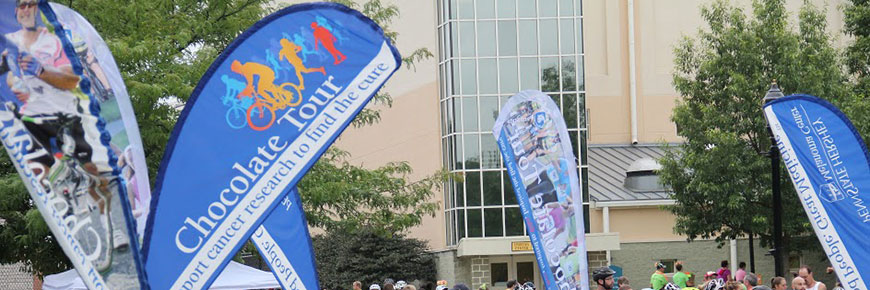 An outdoor banner/sign for the Chocolate Tour featuring silhouettes of cyclists and runners, stands among several others for the tour in an outdoor setting.