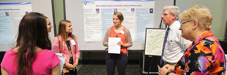 A young female medical student, approximately in her twenties, stands in front of a poster for Penn State Cancer Institute's Shared Resources, addressing three other young female medical students, also in their twenties, and two adults approximately in their fifties.