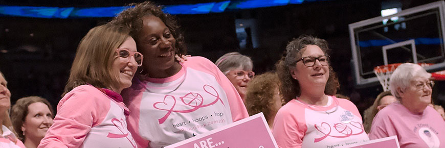 Two women in matching pink shirts pose together for a photo while several other women also in pink tee shirts stand nearby.