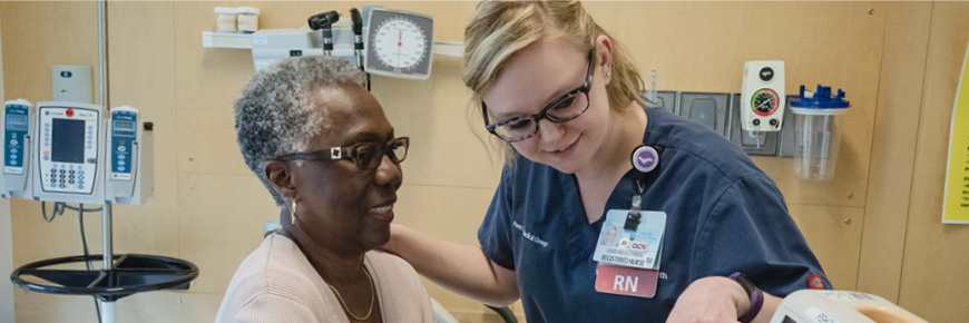 A female RN in blue nurses uniform speaks with an older African American woman in a hospital room.