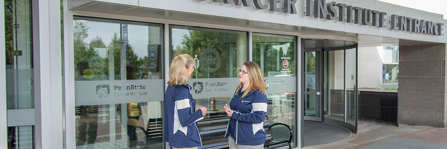 Two females have a conversation at the entrance of the Penn State Cancer Institute