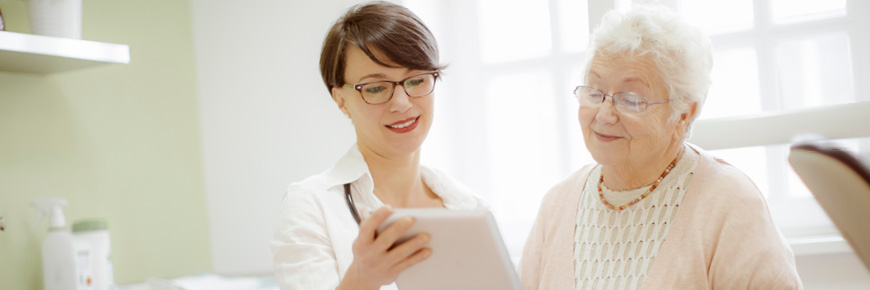 A doctor and her elderly patient look over the patient's results on an iPad.