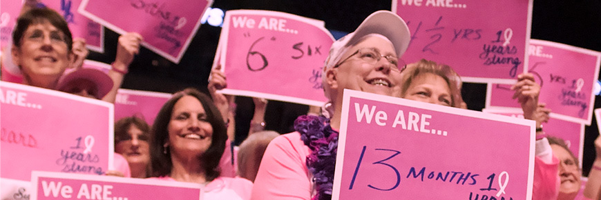 "A group of women all wearing pink and holding fill-in-the-blank pink signs that say ""We ARE …"" stand together."