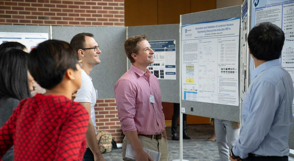 Three men and two woman are pictured talking to each other while gesturing at an academic poster.
