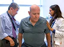 Two medical providers examing a male patient in an exam room.